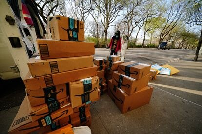 Un hombre mira paquetes entregados por Amazon durante la cuarentena.