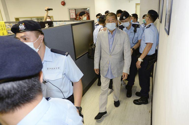 El empresario Jimmy Lai, en el centro, escoltado por la policía en la redacción de 'Apple Daily', este lunes, en Hong Kong.