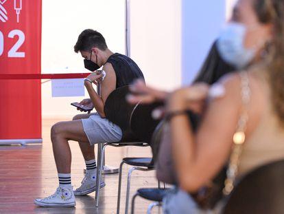 Un adolescente espera en una sala, después de recibir la primera dosis de la vacuna Pfizer en el punto de vacunación de Xátiva, situado en el Hogar de los Jubilados, a 10 de agosto de 2021.