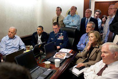 El presidente Barack Obama, junto al vicepresidente Joe Biden (primero por la izquierda) y la secretaria de Estado estadounidense (segunda por la derecha), recibe un nuevo dato de la misión que tenía por objetivo acabar con Bin Laden. En la mesa de la sala,  en la que también se encuentran varios miembros del equipo de seguridad nacional de Obama, se encuentra un documento clasificado que ha sido pixelado para evitar su divulgación.