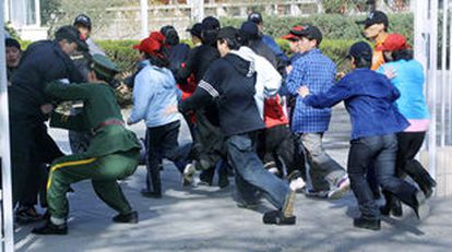 Un policía chino trata de impedir la entrada del grupo de norcoreanos a la embajada española.