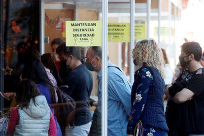 Varias personas aguardan su turno en un mercadillo de Valencia, debidamente señalizado con las medidas anticovid, a menos de dos semanas de celebrarse la navidad.
