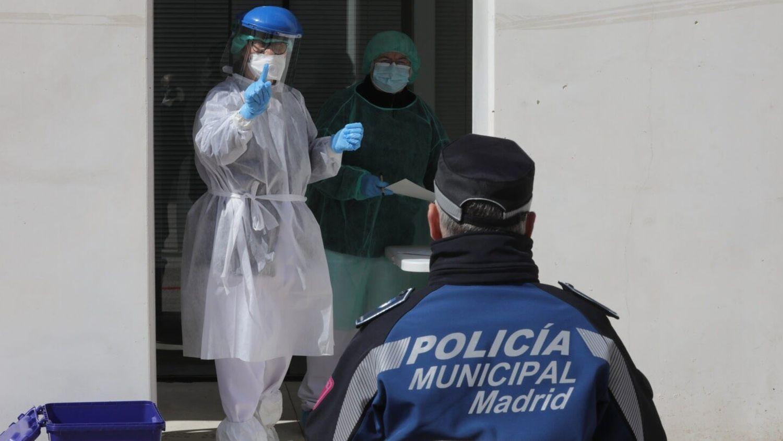 Dos sanitarias efectúan este miércoles en Madrid el test del coronavirus a una policía municipal en el pabellón de Casa de Campo.