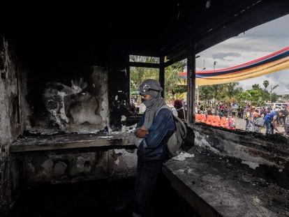 Un joven monta guardia en el interior de una estación de Policía que fue quemada por los manifestantes en Puerto Resistencia, Cali, este miércoles.