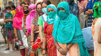 Mujeres indias esperan en una cola de reparto de raciones de comida.