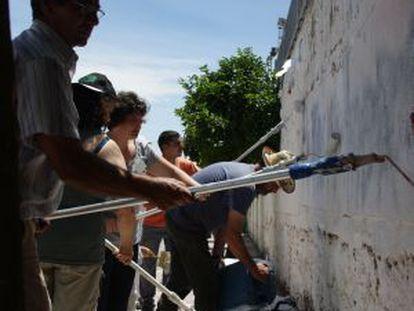 Unos vecinos encalan el muro del polideportivo en Higuera de la Serena.