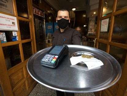 Eduardo, camarero del bar Cantalejo en Madrid, muestra la propina que ha dejado un cliente.