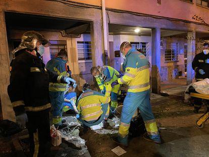 Sanitarios y bomberos atienden a la mujer, tendida en el suelo frente a la vivienda incendiada.
