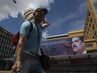 Un hombre con cubrebocas camina frente a una imagen de Nicolás Maduro en el centro de Caracas, el 6 de julio.