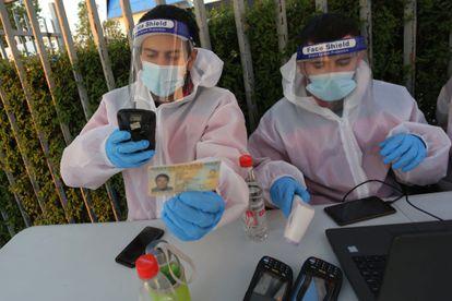 Personal médico en Chile registra un documento de identidad como parte del protocolo contra la covid-19 antes de un partido de fútbol.