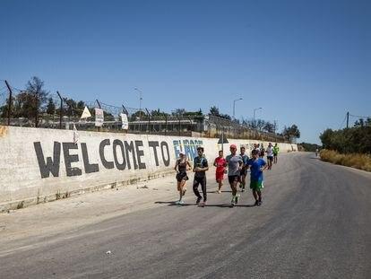 El equipo de corredores de la ONG Yoga y Deporte con Refugiados pasa junto al muro del antiguo campamento de refugiados de Moria, cerrado después del incendio de 2020.