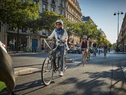 Varias personas pedalean por un carril bici de París.