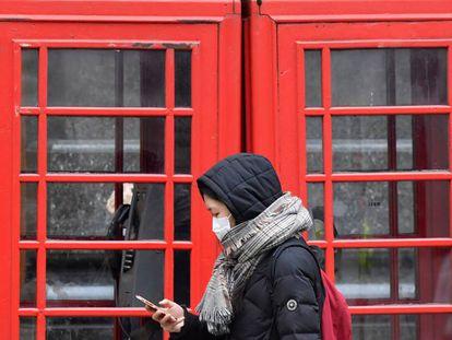 Una mujer con mascarilla protectora revisa su teléfono móvil mientras camina por Londres.