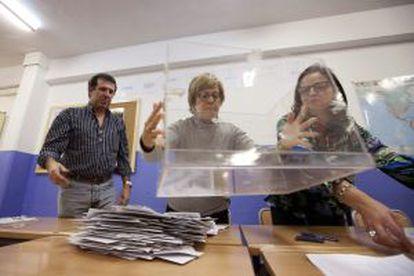 Miembros de una mesa electoral en un colegio de Vitoria vacían la urna.