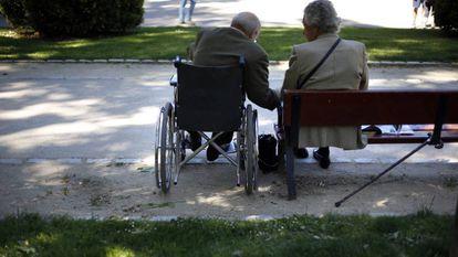 Dos ancianos sentados en un parque.