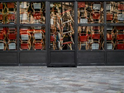 Sillas apiladas tras las puertas de un restaurante cerrado en París a causa de la epidemia de coronavirus