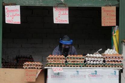 Una mujer se protege la covid-19 en su puesto de venta de huevos en Quito (Ecuador).