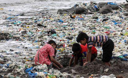 Varios niños juegan entre desechos de comida y plástico cerca de la costa del mar Arábigo, en la playa de Mahim, en Bombay (India)
