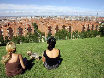 Dos mujeres observan la vista del Puente de Vallecas desde el parque del Cerro del Tio Pío, en Madrid.