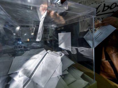 Una mujer introduce su voto en una urna en Girona.
