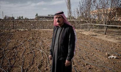 Un agricultor iraquí junto a su terreno, seco, al lado de un canal de irrigación.