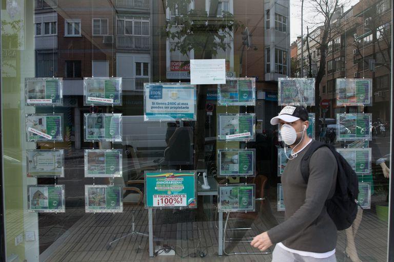 Un hombre pasa ante una inmobiliaria cerrada durante el estado de alarma, en Madrid.