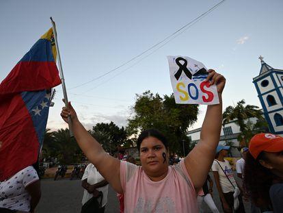 Una mujer sostiene la bandera de Venezuela en una protesta por la muerte en un naufragio de migrantes venezolanos, el 17 de diciembre.