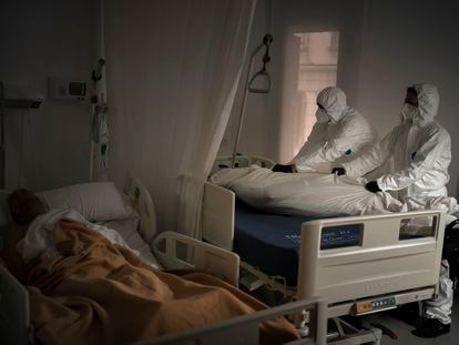 Dos profesionales de una funeraria mueven el cuerpo de un anciano fallecido por coronavirus en una residencia de Barcelona, el pasado noviembre.