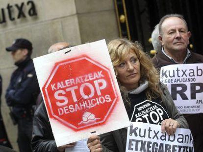 Miembros de Kaleratzeak Stop Desahucios e IRPH-STOP de Gipuzkoa participan en una concentración frente a la sede de Kutxabank en San Sebastián.