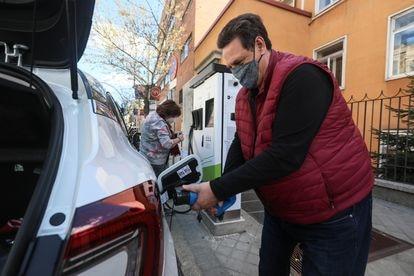 Un usuario recarga su coche eléctrico en un punto situado en la calle en el centro de Madrid.