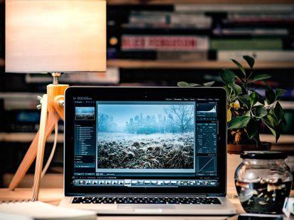 Un ordenador junto a una lámpara en la mesa de un despacho.