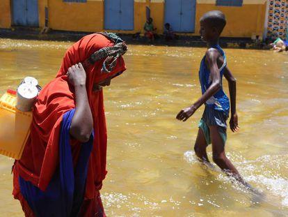 Una mujer y un niño caminan entre el agua tras una inundación.