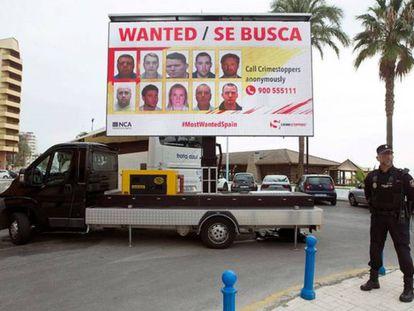 Un policía delante de una de las vallas en las que se exhiben las caras de los delincuentes más buscados de la Costa del Sol.