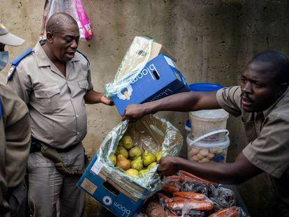 Dos agentes de la policía de Gauteng confiscan los alimentos que un hombre vende en su puesto callejero en el suburbio de Alexandra, en Johanesburgo, Sudáfrica, el 31 de marzo de 2020. Con el país en cuarentena, son muchos los se quedan sin medios de subsistencia si no pueden salir a la calle.