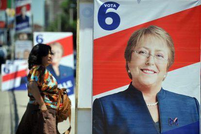Una mujer camina al lado de la propaganda política de Bachelet.