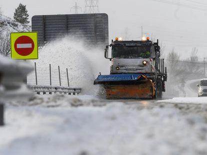 Una máquina quitanieves limpia la A-67, donde varios camiones quedaron atrapados el sábado en la localidad cántabra de Arenas de Iguña.