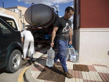 Un vecino de Fuente de Piedra (Málaga) recoge agua de un camión cisterna para abastecerse en 2019.