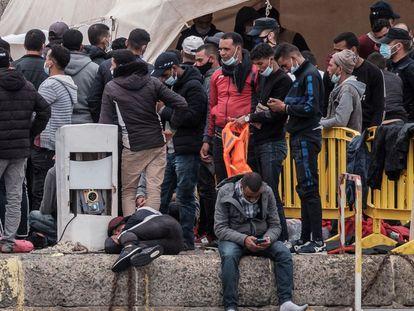 Varios inmigrantes se agolpan en el puerto de Arguineguín, en Gran Canaria, después de que Salvamento Marítimo rescatara durante la madrugada del pasado sábado a 294 inmigrantes de once pateras.