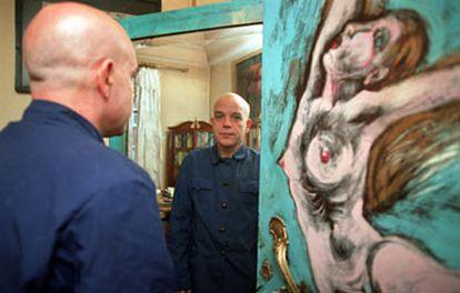 Jesús Ferrero, en su casa de Madrid, junto a una pintura de Irene Gracia.