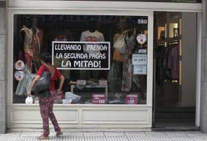 Una mujer observa la vitrina de un almacén de ropa el 29 de enero de 2014, en el centro de Buenos Aires.