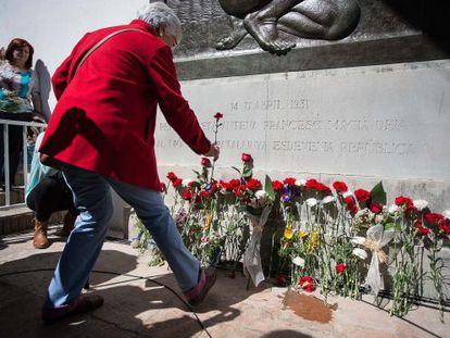 Una persona coloca una flor delante del monumento a la República.