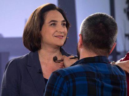 Un maquillador retoca a la candidata a la alcaldía de Barcelona, Ada Colau (BComú), antes de celebrar el debate electoral organizado por Betevé y la Federación de Asociaciones de Vecinos de Barcelona.