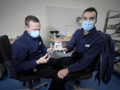 Óscar de la Cruz (izquierda) y Mario Ochescu, trabajadores de Escribano, muestran el corazón mecánico del respirador VITAE 40 en la fábrica de la empresa, en Alcalá de Henares (Madrid).