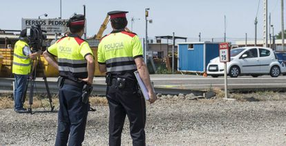 Dos 'mossos' vigilan una carretera en Juneda (Lleida).