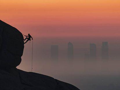 El bombero Antonio Marcos escala con las Cuatro Torres de fondo. Pincha sobre la imagen para ver más fotos de este 'skyline'.