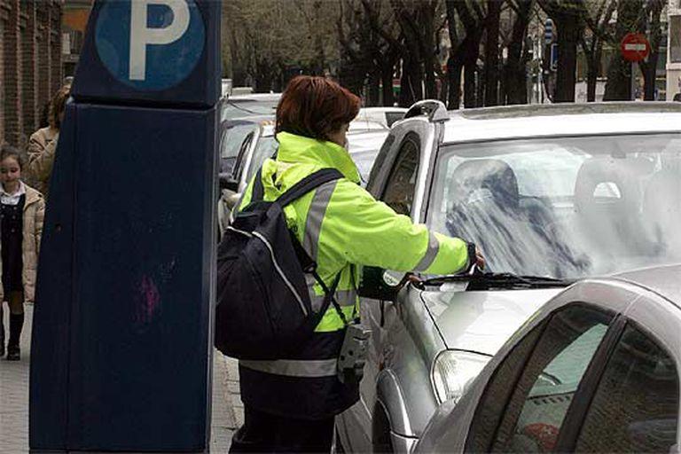 Una controladora de los parquímetros coloca una denuncia en el parabrisas de un turismo en la calle de Juan Bravo.