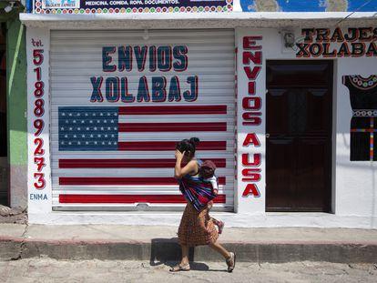 Una mujer pasa con su hijo frente a un local de envíos hacia y desde EE UU en Joyabaj (Guatemala).