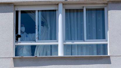 Un agente de la policía nacional corre una cortina en la vivienda del suceso en Úbeda (Jaén), este domingo.