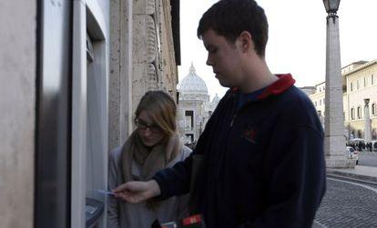 Un hombre saca dinero de un cajero junto al Vaticano.