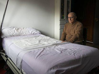 Ángel Hernández, junto a la cama en la que ayudó a morir a su mujer, María José Carrasco, enferma de esclerosis múltiple, en su casa de Madrid.